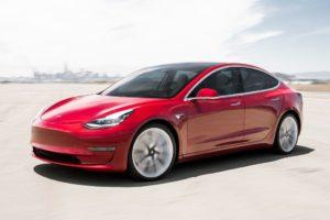 Tesla Model 3 rojo curva aeropuerto